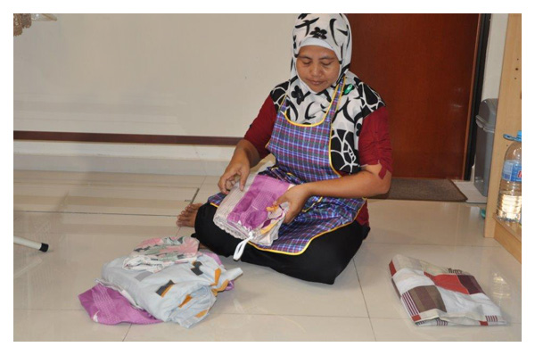 indonesian maid from singapore maid agency folding clothes